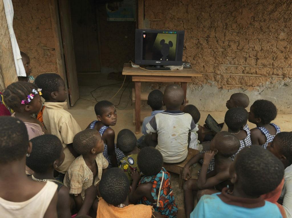I bambini figli dei lavoratori di CAYAT, in Costa D'Avorio attorno alla televisione acquistata con i soldi del Premio. a Baoulekro, un villaggio locale di 300 persone. ©Peter Caton